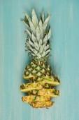 """Постер, картина, фотообои """"вид сверху нарезанный желтый ананас на бирюзовый деревянный стол"""""""