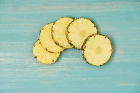 top view of sliced pineapple circles on turquoise wooden table