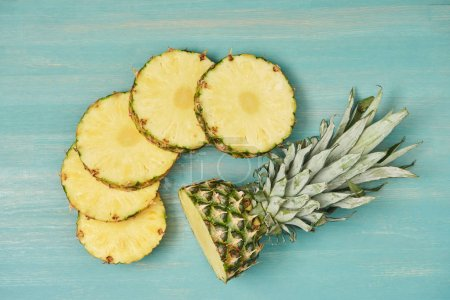 top view of sliced pineapple circles near cut pineapple on turquoise wooden table