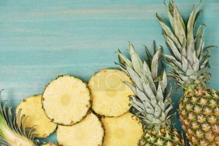 Foto de Vista superior de la piña en rodajas y todo sobre mesa de madera turquesa - Imagen libre de derechos