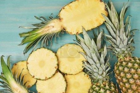 Foto de Vista superior de piñas enteras y en rodajas en mesa de madera turquesa - Imagen libre de derechos