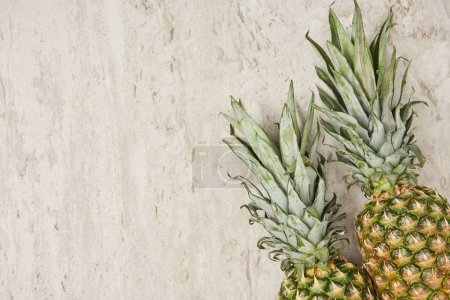 top view of organic and tasty pineapples on marble background