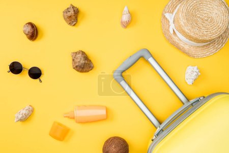 Photo for Top view of seashells, coconut, sunglasses, luggage and straw hat on yellow background - Royalty Free Image