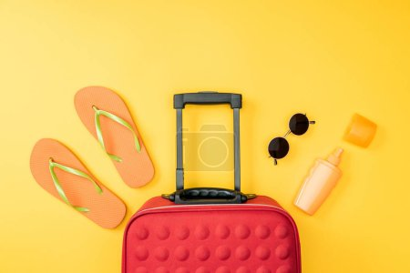 top view of travel bag, flip flops and sunglasses on yellow background