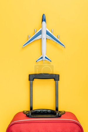 Photo for Top view of red baggage and toy plane on yellow background - Royalty Free Image