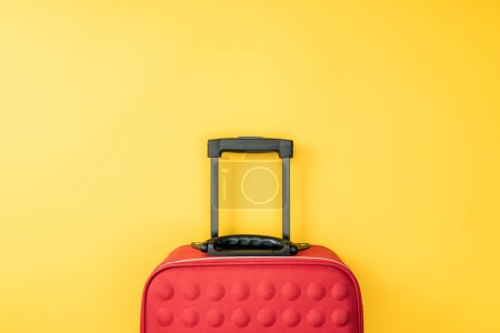 top view of red travel bag on yellow background