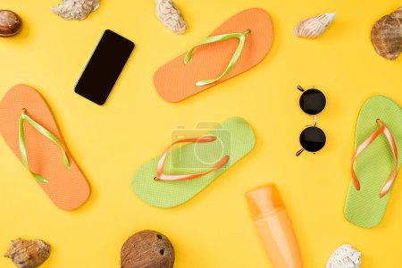 top view of smartphone with blank screen, sunglasses, coconut, flip flops and seashells on yellow background