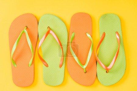 Photo pour Vue de dessus du coloré flip flops sur fond jaune - image libre de droit