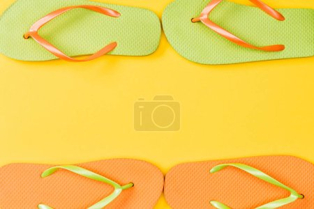 top view of flip flops on yellow background