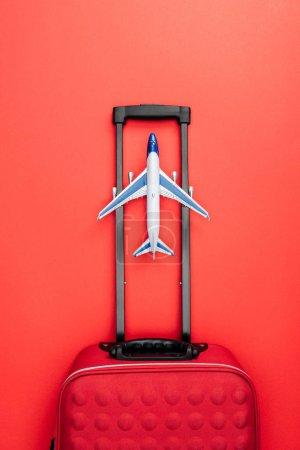 Foto de Vista superior de la bolsa de viaje con manija y juguete plano sobre fondo rojo - Imagen libre de derechos