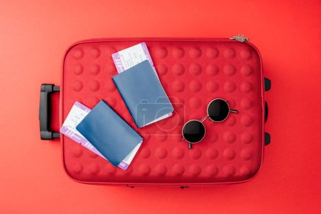 Photo for Top view of travel bag, passports, air tickets and sunglasses on red background - Royalty Free Image