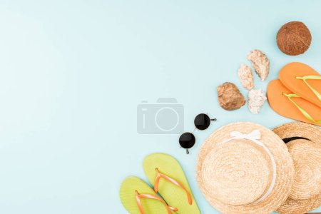 top view of sunglasses, flip flops, straw hats and seashells on blue background
