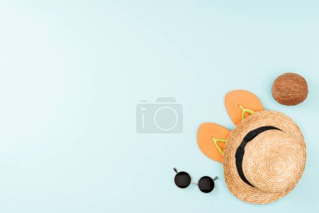 top view of sunglasses, flip flops, straw hat and coconut on blue background