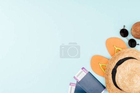Photo for Top view of sunglasses, flip flops, straw hat, coconut and passports with air tickets on blue background - Royalty Free Image