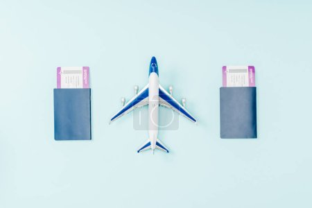 top view of passports, air tickets and toy plane on blue background