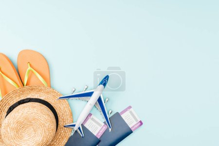 Photo for Top view of passports, air tickets, straw hat, flip flops and toy plane on blue background - Royalty Free Image