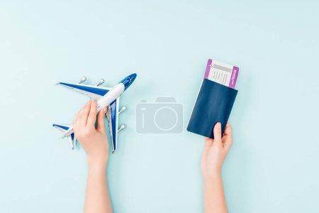 Photo pour Recadrée vue de femme, détenteurs d'un passeport, de l'air avion billet et jouet sur fond bleu - image libre de droit