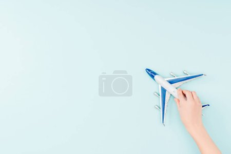 cropped view of woman holding toy plane on blue background