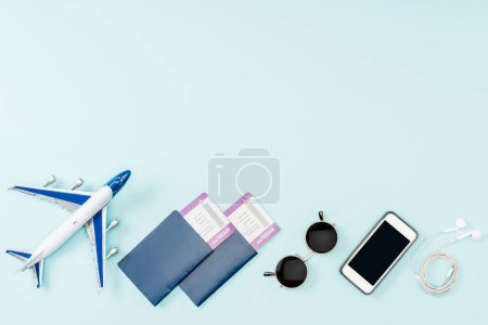top view of passports, air tickets, toy plane, smartphone with blank screen, earphones and sunglasses on blue background