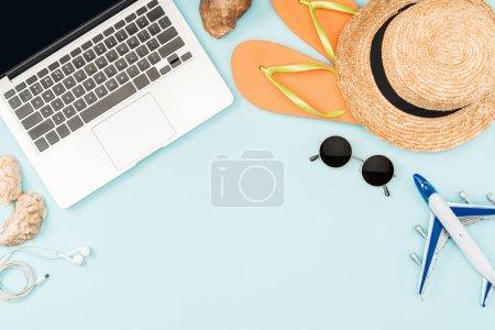 vue du dessus de l'avion jouet, ordinateur portable avec écran blanc, écouteurs, lunettes de soleil, coquillages, tongs, modèle d'avion et chapeau de paille sur fond bleu