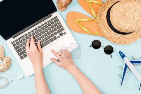 Photo pour Recadrée vue de femme à l'aide d'ordinateur portable près d'écouteurs, de lunettes, de coquillages, flip flops, peinture bleue et chapeau de paille sur fond bleu - image libre de droit