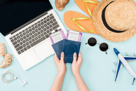 Photo for Cropped view of woman holding passports and air tickets near laptop, earphones, sunglasses, seashells, flip flops and straw hat on blue background - Royalty Free Image