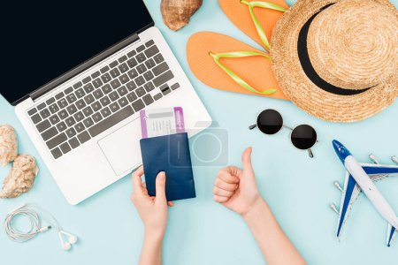 Photo for Cropped view of woman holding passports and air tickets while doing thumb up gesture near laptop, earphones, sunglasses, seashells, flip flops, toy plane and straw hat on blue background - Royalty Free Image