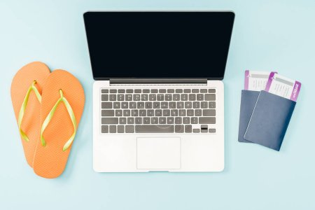 top view of laptop with blank screen, flip flops and passports with air tickets on blue background
