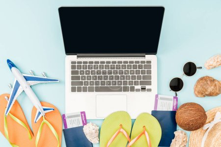 top view of laptop with blank screen, flip flops, passports with air tickets, sunglasses, seashells, straw hat and plane toy on blue background