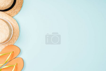 Foto de Vista superior de sombreros de paja y chanclas sobre fondo azul - Imagen libre de derechos