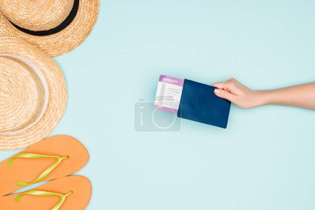 cropped view of woman holding air ticket and passport near flip flops and straw hats on blue background