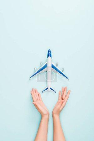 Photo pour Vue recadrée de la femme tenant la main près de l'avion jouet sur fond bleu - image libre de droit