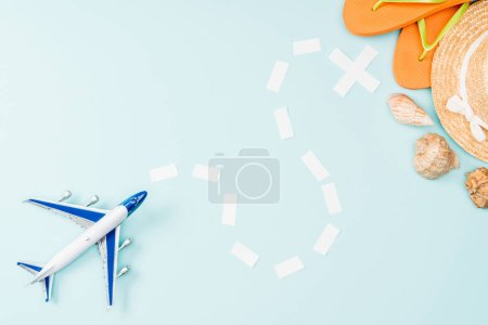top view of toy plane, dotted line, straw hat, seashells and flip flops on blue background