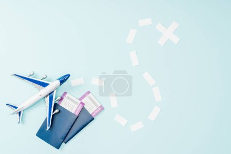 top view of toy plane, dotted line, air tickets and passports on blue background