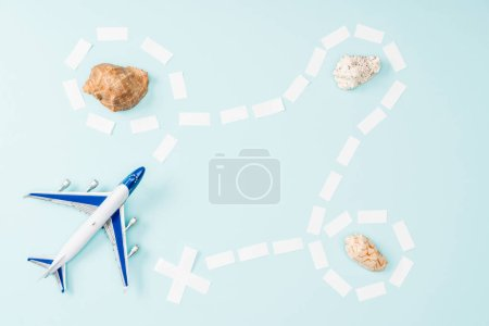 Photo for Top view of toy plane, dotted line and seashells on blue background - Royalty Free Image