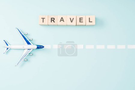 top view of toy plane, dotted line and wooden cubes with travel lettering on blue background
