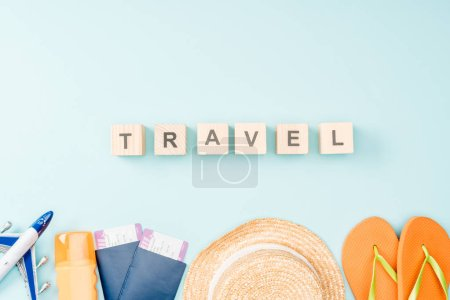 top view of wooden cubes with travel lettering, straw hat, flip flops, passports and air tickets on blue background