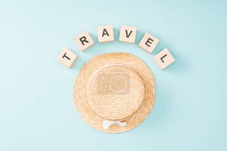 top view of wooden cubes with travel lettering and straw hat on blue background