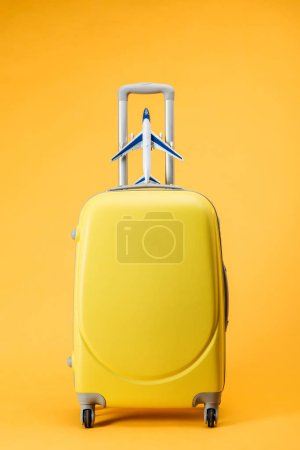 travel bag with wheels and toy plane on yellow background