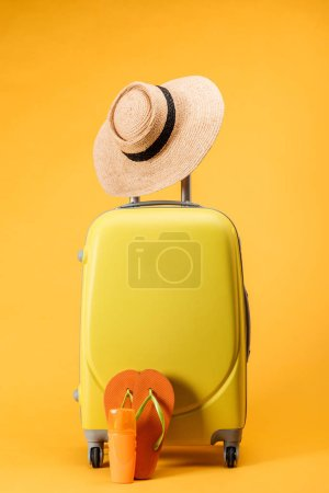travel bag with wheels, straw hat and flip flops on yellow background
