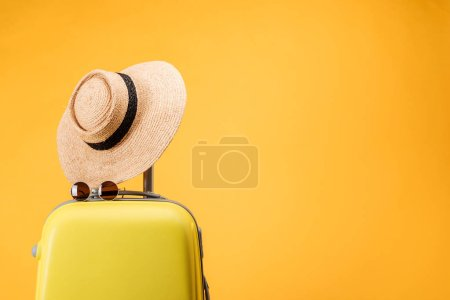Photo for Travel bag, straw hat and sunglasses isolated on yellow - Royalty Free Image