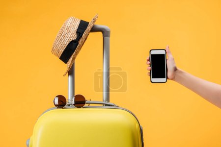 Photo pour Vue recadrée de la femme tenant smartphone avec écran vierge près du sac de voyage, chapeau de paille et lunettes de soleil isolées sur jaune - image libre de droit