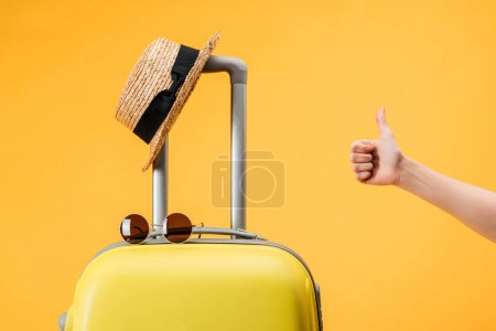 cropped view of woman doing thumb up gesture near travel bag, straw hat and sunglasses isolated on yellow