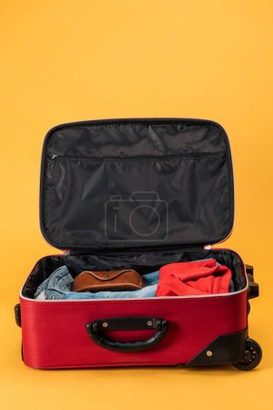 Photo for Case and clothes in travel bag on yellow background - Royalty Free Image