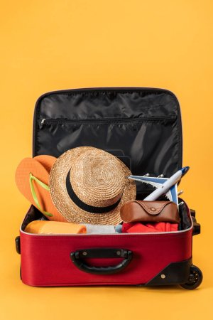 Photo for Toy plane, straw hat, flip flops and clothes in travel bag on yellow background - Royalty Free Image