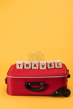 travel bag and wooden cubes with travel lettering on yellow background