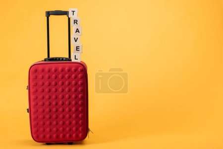 travel bag with wheels and wooden cubes with travel lettering on yellow background