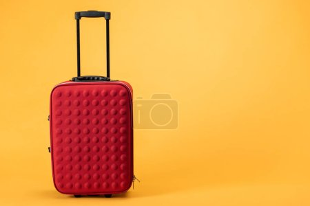 red travel bag with wheels and handle on yellow background