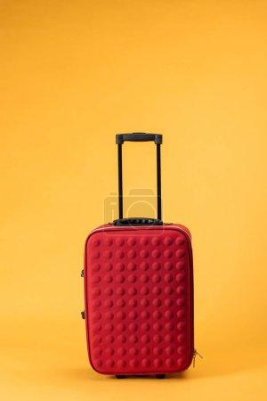 Photo pour Sac de voyage rouge avec roues sur fond jaune - image libre de droit