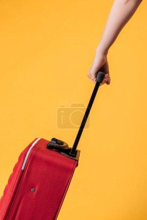 Photo pour Vue recadrée de femme avec sac de voyage rouge isolé jaune - image libre de droit